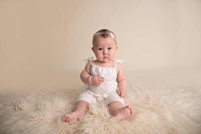 a baby wearing white romper and dainty tieback sits on fur rug looking at camera