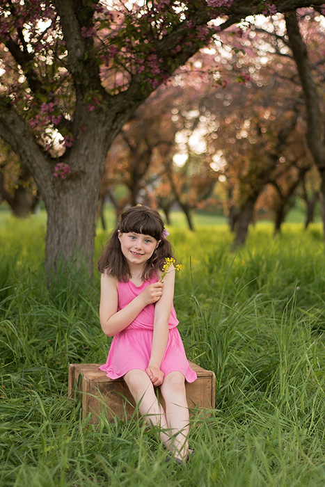 a girl sits on a wood box under a blooming tree at lincoln fields in ottawa