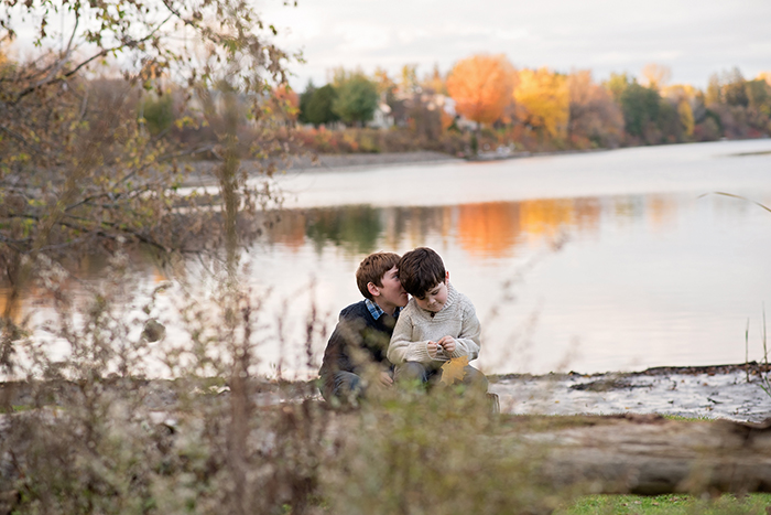 two brothers sit together by water at balck rapids in ottawa one whispering into the other ones ear with the fall trees in the background