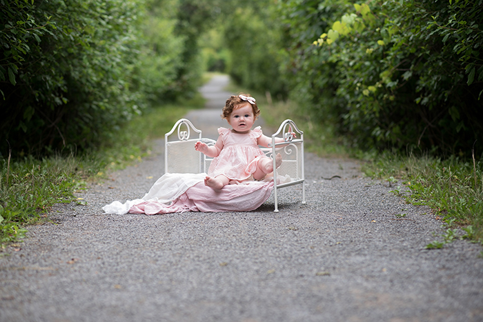 a baby sits outside on a white iron bed looking at the camera