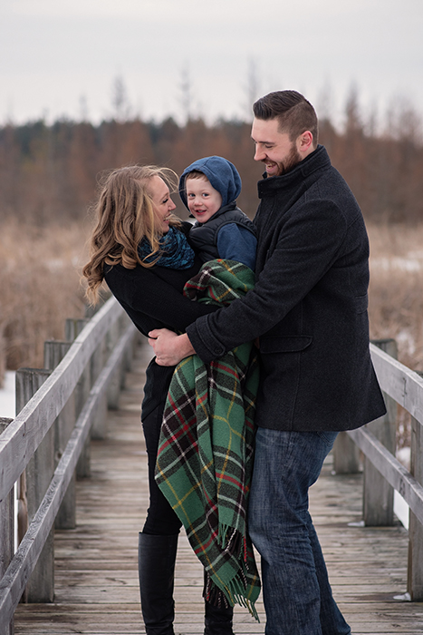a family stands on a wood bridge in the winter wrapped in a plaid blanket at mer bleu in orleans candidly smiling at each other