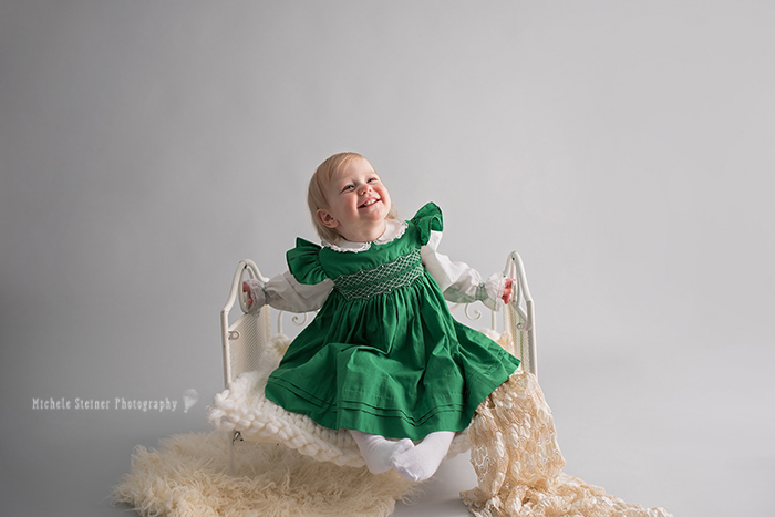 a girl sits on a white iron bed wearing a green old fashioned vintage dress smiling off to the side in ottawa photography studio for her milestone session