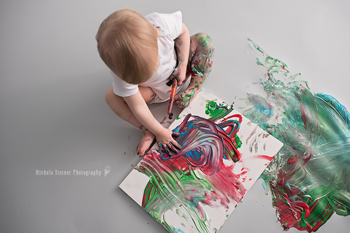 view from above a girl sits painting with her hands a colourful canvas for her one year milestone photography session in ottawa studio