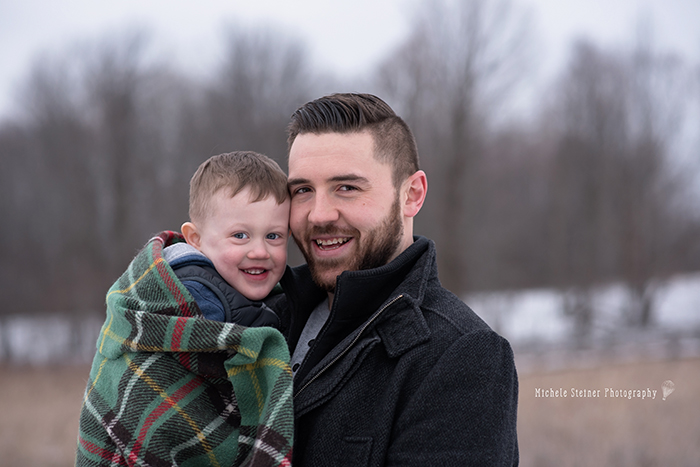 a father holds his son in his arms both smiling at camera with toddler wrapped in a plaid blanket in winter