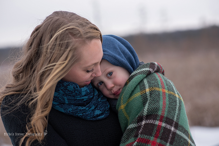 a mother holds her son looking down at him as his face rest on her body outside in winter in ottawa