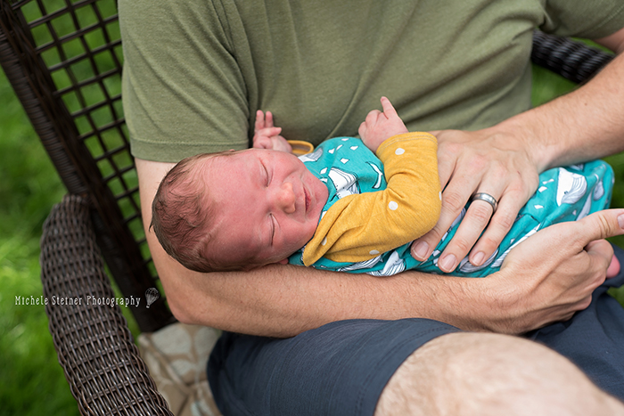 a father holds his newborn in his arms outside his home sitting in a chair baby is sleeping