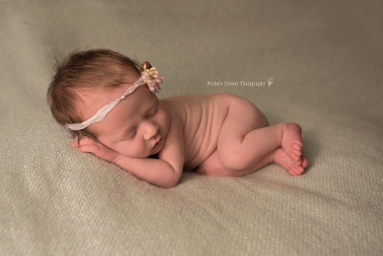 a newborn girl in a side lying pose on a green blanket with a pinecone natural tieback