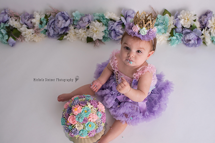 a top view of a baby girl sitting with her cake for her milestone session icing on her figners and face