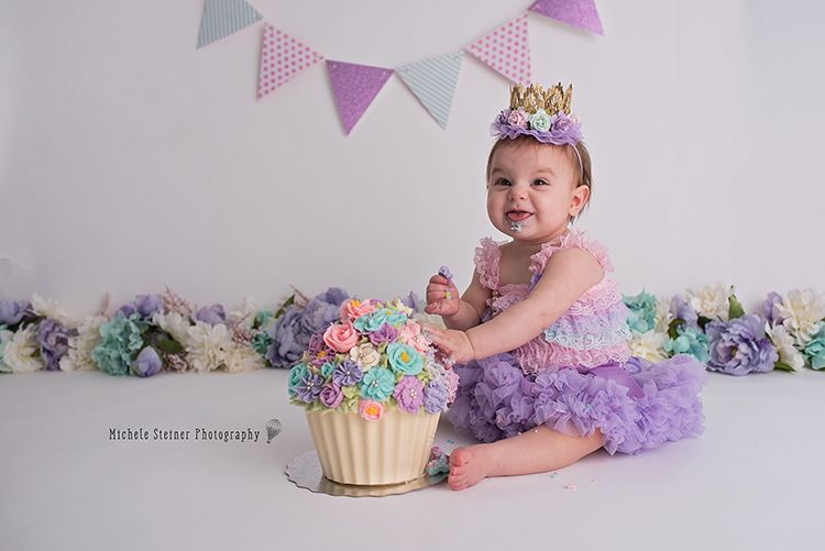 a little girl sits with her floral cake for milestone cake smash session silly expression tongue out