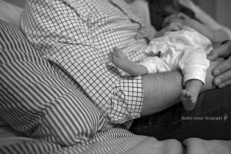 a father holds his newborn daughter her feet hanging over his arm