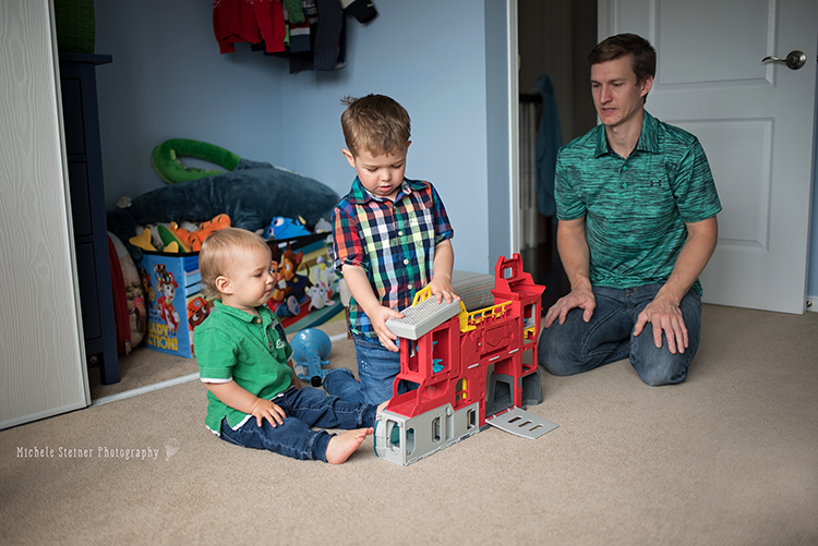 a family sits together on the floor in a bedroom playing with toys brothers looking down