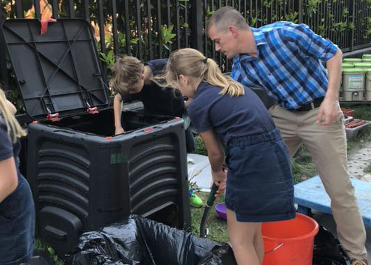 Science-Technology-Engineering-Math Coach Ryan Maney oversees the transfer of the compost that was derived from food waste.
