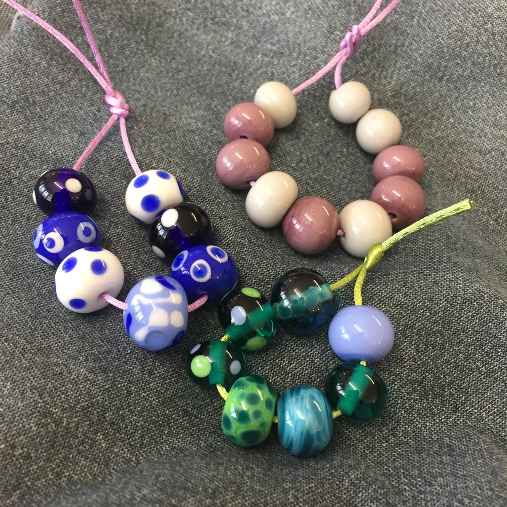 Susan's beads (bottom of picture) were made on a half-day beginners' course, and have been strung in the order in which they were made. Rosie's beads were made independently of any tuition, as she built on her existing experience at the torch flame to work on her own projects.