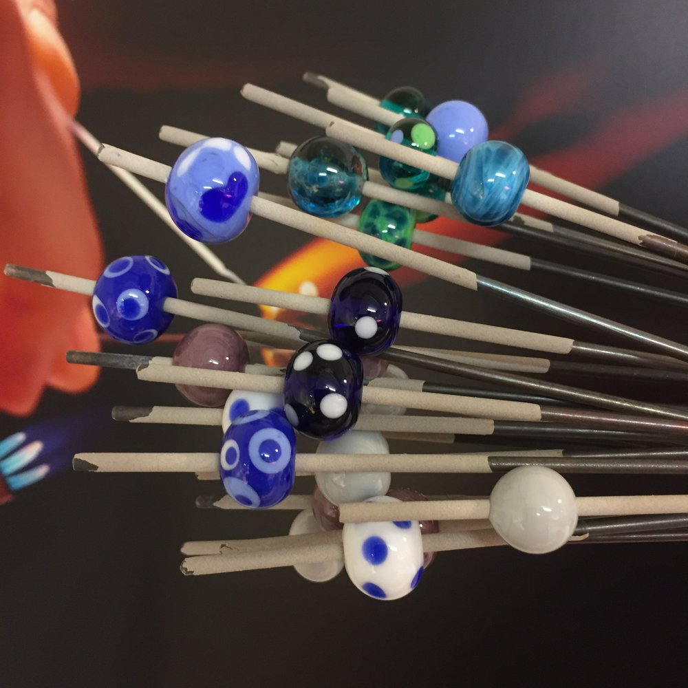 Here are the beads as they came out of the kiln having been annealed overnight for lasting strength - an essential part of any hot-glass making. As you can see, they are still on their mandrels. The powdery-grey coating on the mandrels (which makes them look rather like sparklers!) is called 'bead release' or 'bead separator' and is a sacrificial layer of clay between the steel of the mandrel and the glass bead itself. The layer is applied anew each time a mandrel is used. Beads are removed from the mandrels by dunking them in water, holding really tight with pliers and gently gripping and turning the bead. The final step is to file the residue of the bead release from the bead holes - also a job for underwater! The powder is harmful if breathed in, so it is absolutely essential to remove it.