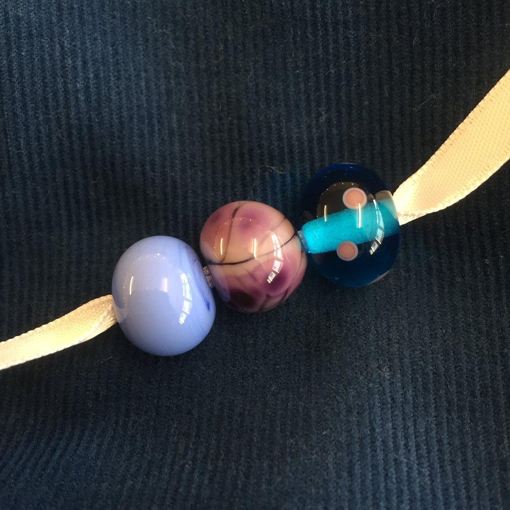 My snap of Corinne's finished collection of three beads. My favourite is the middle one - she decorated a mauve bead with some gorgeous reactive purple frit, and it's come out beautifully!