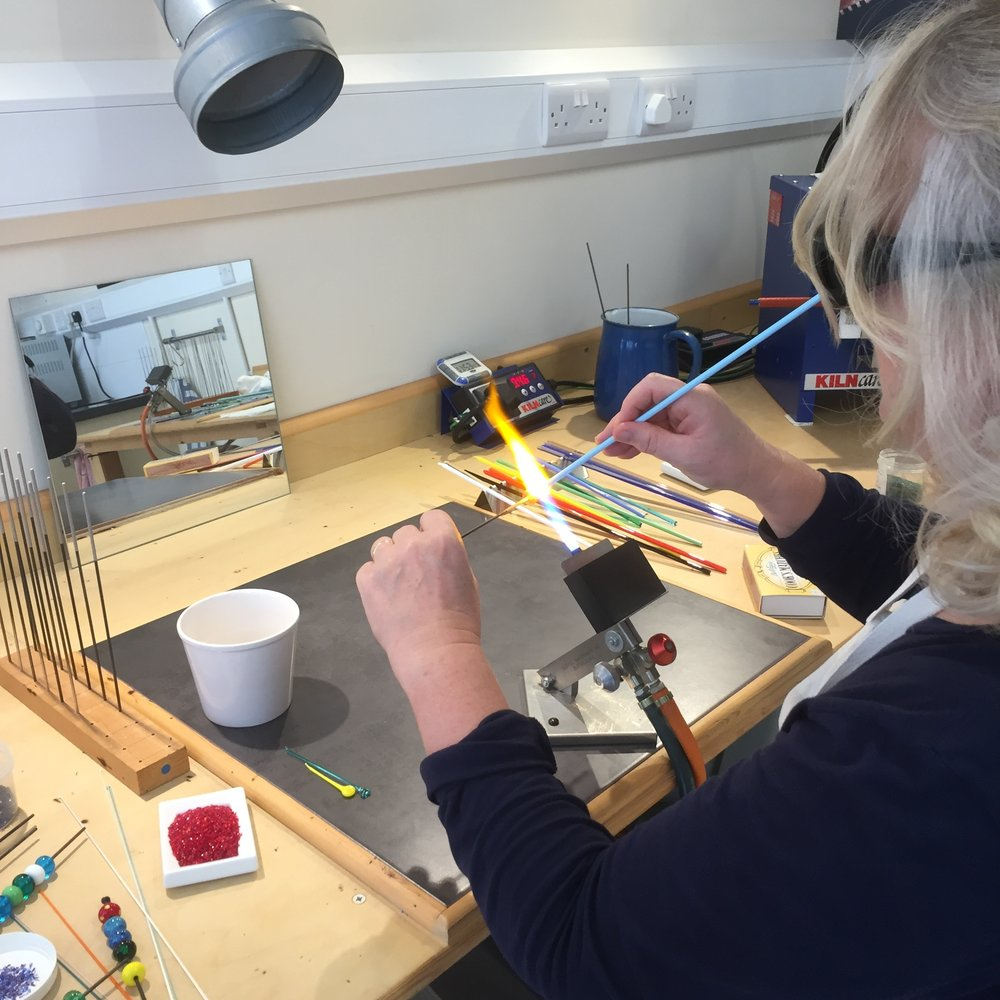 Here's Sarah winding a bead at the torch flame - the dish of red frit on the left-hand side is destined for surface decoration.