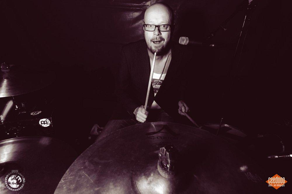 Dominiek De Decker  Als klassiek geschoold trombonist en drummer ontwikkelde hij al snel een grote interesse in de pop- en rockmuziek. Als trombonist ging Dominiek onder andere op tournee met het Caravelli Orchestra in Japan en versterkte ook allerlei blazerssecties. Voor het moment is Dominiek aan de slag bij M'nB's (hip-hop), les Sacs à Sacs (Franse Chansons), ...