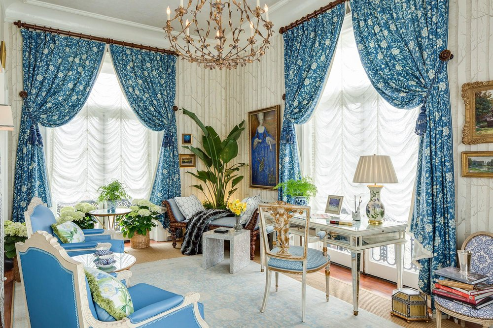 Luxury living room with blue painted curtains and chandelier