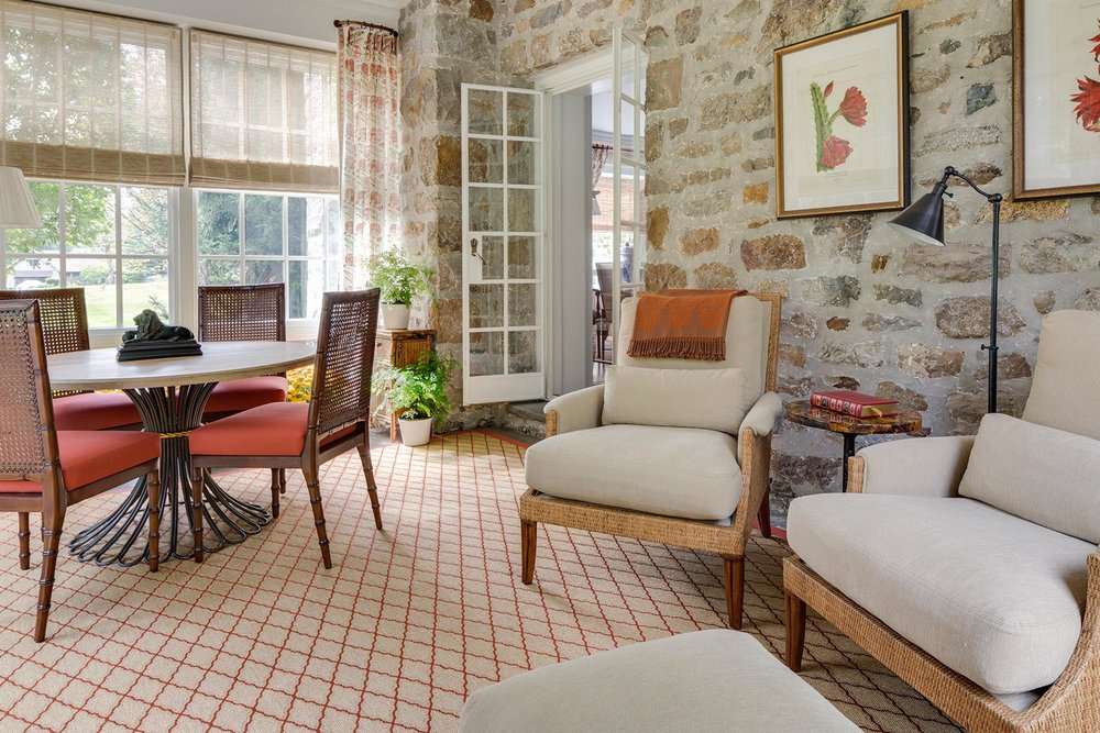 Bright living room with chairs and stone wall