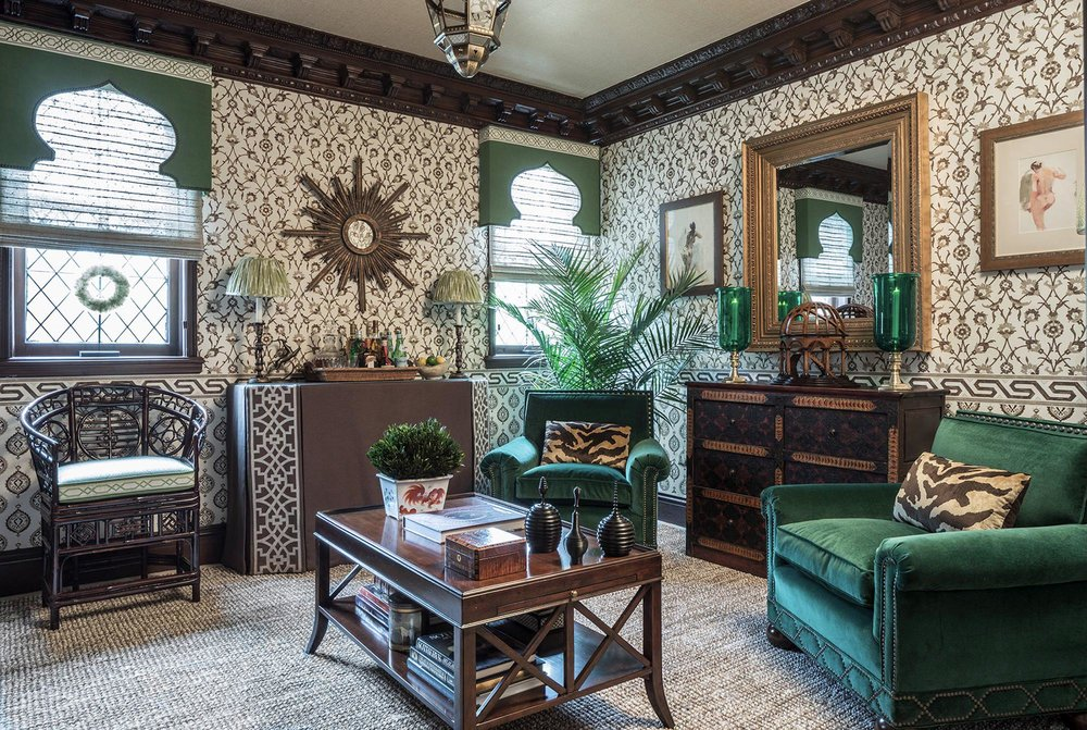 Vintage style living room with green couches and stylish wall designs