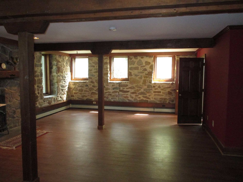 Spacious room with wooden floor and stone style wall