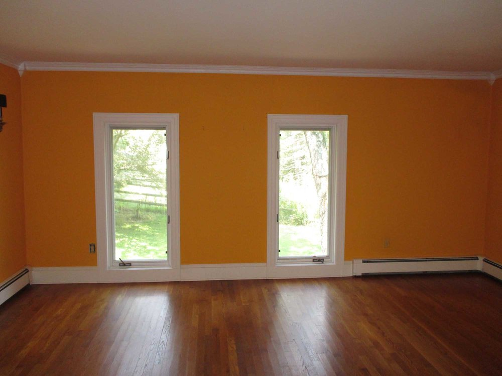 Spacious room in orange paint and wooden floor