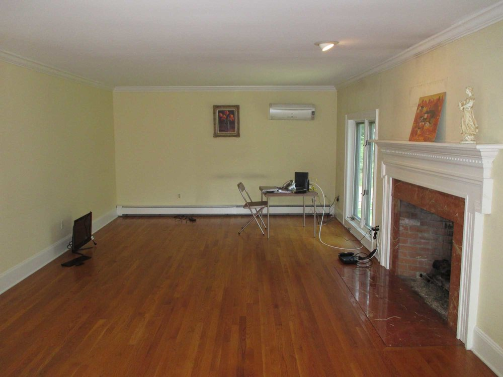 Empty living room with fireplace and wooden floor