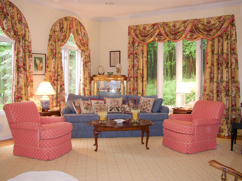 Bright living room with printed curtains and pink and blue sofa
