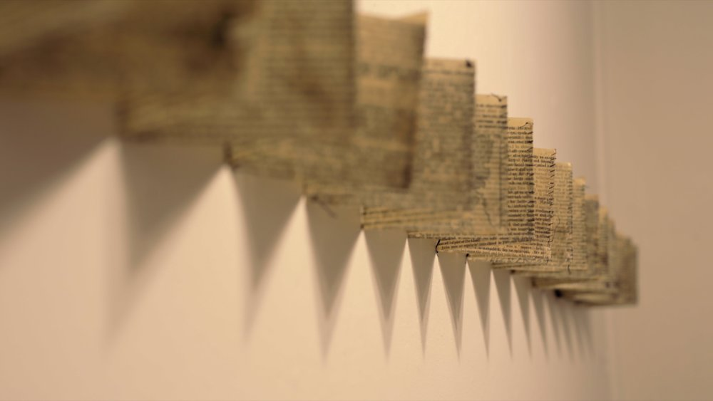 """History of England stitched and folded  (detail) / Book pages, beeswax, thread / 10 cm (4"""") x variable width (this installation 250 cm [9'] ) / 2018"""
