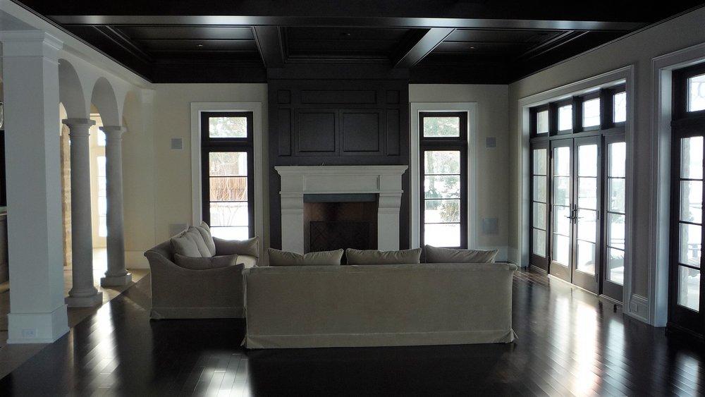 Living area walnet hardwood floor fireplace white mantle.JPG