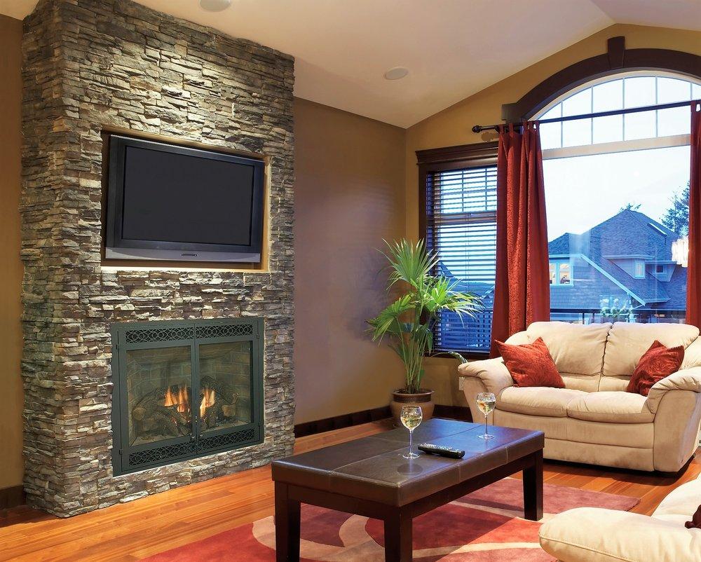 Living area stone fireplace surround hardwood floors carpet area rug.JPG