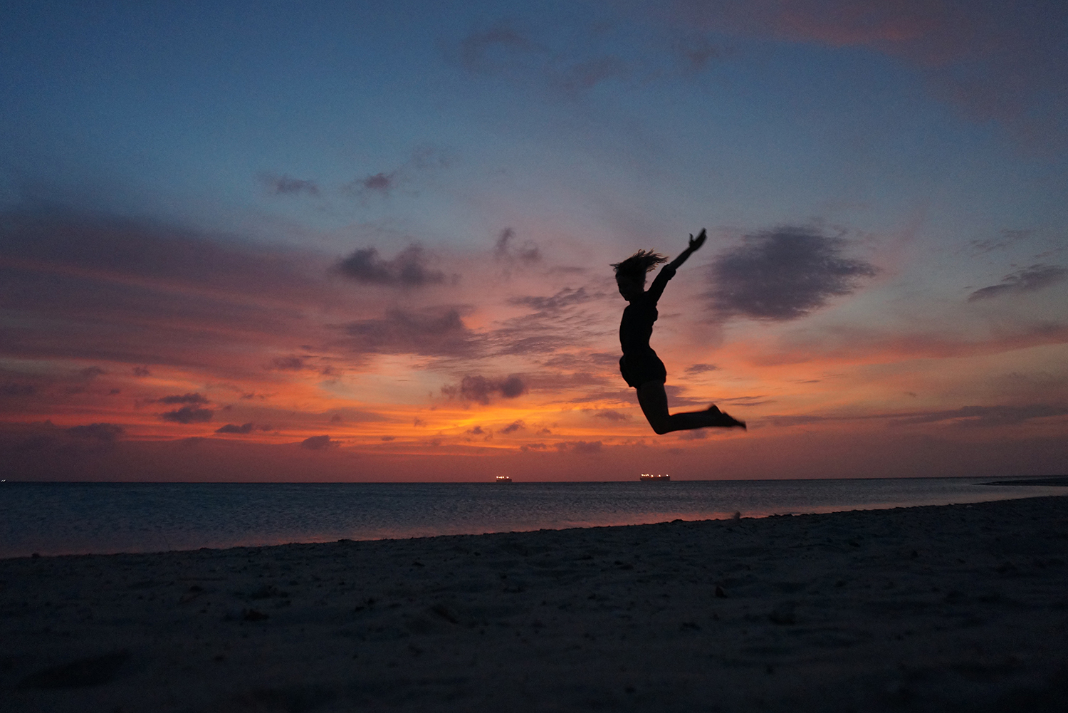 girl jumping silhouette sunset