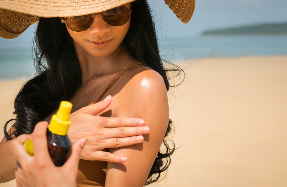 Close - up of Sexy asian woman are Spray Sunscreen , lotion or sunblock to body for prevent UV rays from sunlight Before the sun bathing in the summer or Vacation with sea and bluesky bckground.