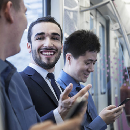 Three business men having a fun conversation on the metro.