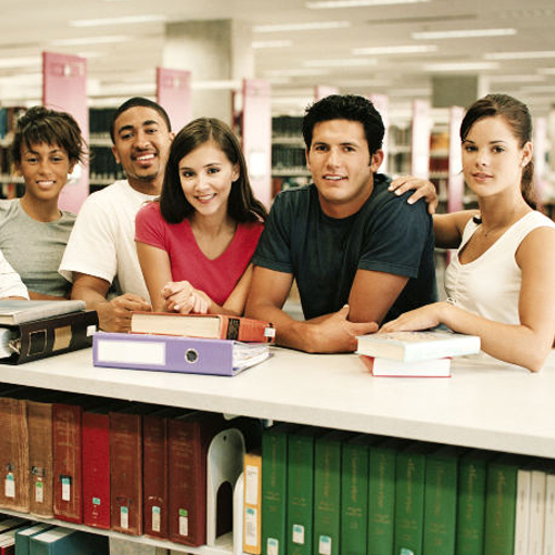 Five People leaning on a counter in a library