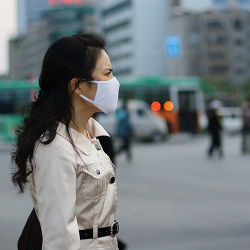 Woman with mask in polluted city