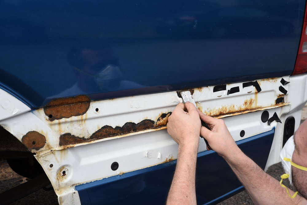 Ian's dad scrapes away some huge patches of rust underneath the plastic trim panels. For some reason these areas remained the original white color when the van was repainted blue by the previous owner,