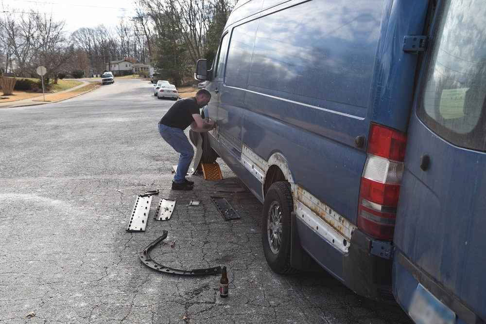 Ian's dad, Brian, removes the crusty, brittle fasteners that attach the plastic trim to the van.