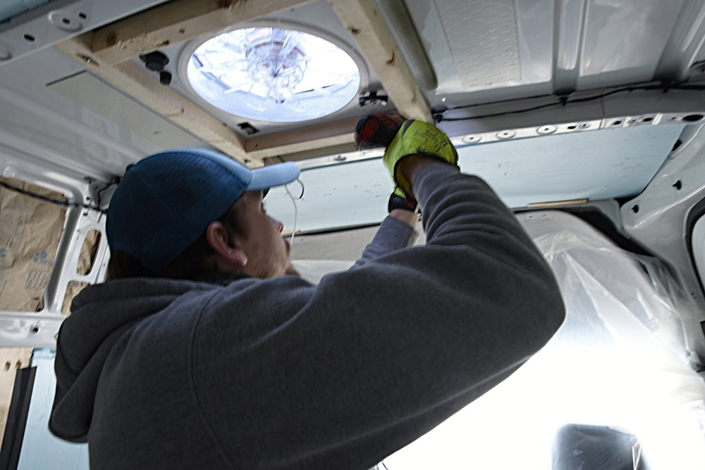 Ian screws the vent frame into place.