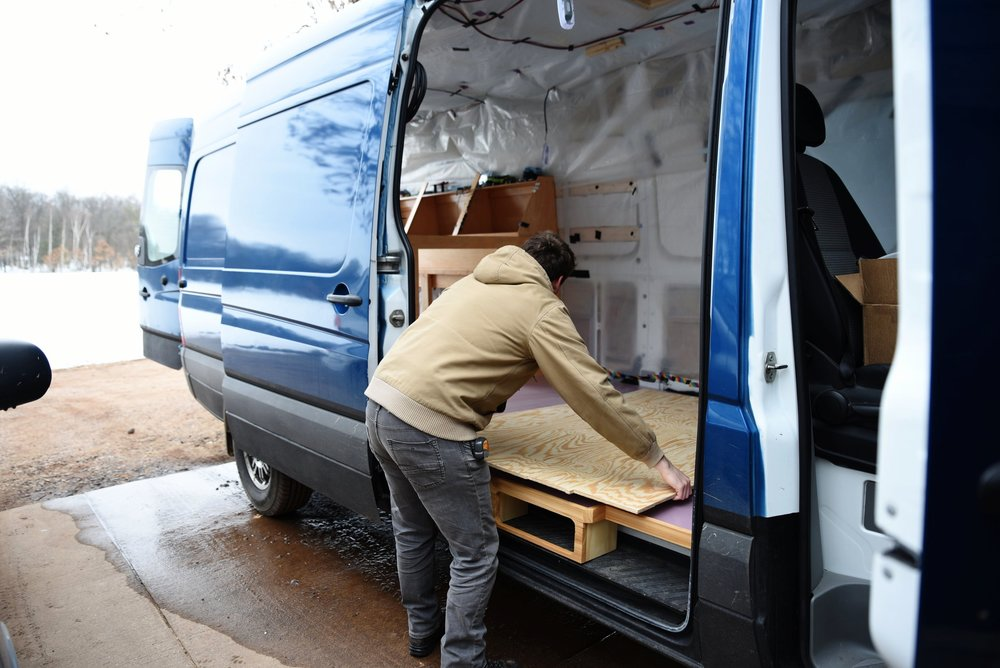 Ian lays the plywood underlayment portion of the flooring in the van.