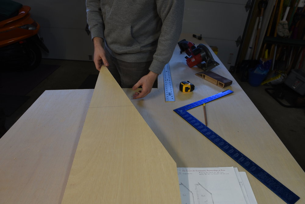 Ian shows the uprights that separate the cupboards of our bedside cabinetry. The left side of the board matches the curve of the van wall, and the right side is angled to provide the shape for a comfortable backrest.