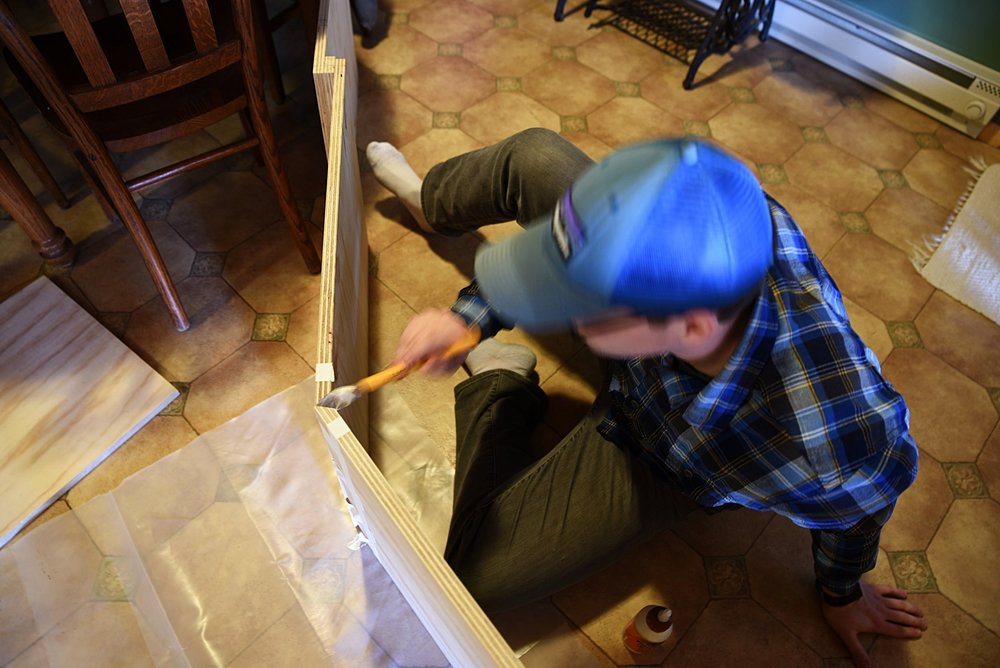 Ian paints wood glue into the 45 degree corner joints. The 45 degree joints give the bench a really nice seamless look.