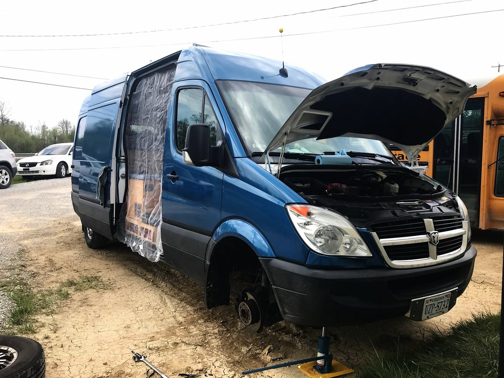 A picture of the van mid-repair. (Ian replaced a brake sensor as well while we were waiting at the shop, that's why the van is jacked up and the wheel is off.)