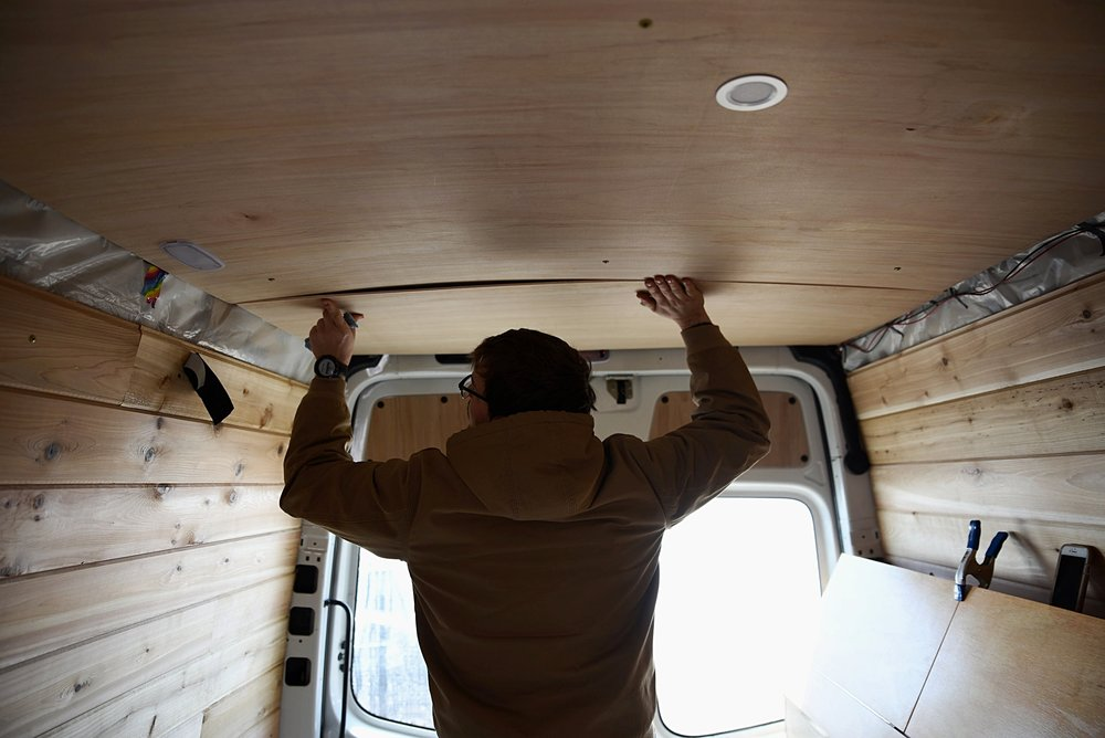 Ian test fits the final ceiling panel before screwing it to the wood lath underneath.