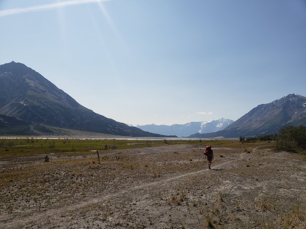 Kaylee hikes toward the mountains of the Kluane Ranges at the end of the valley.