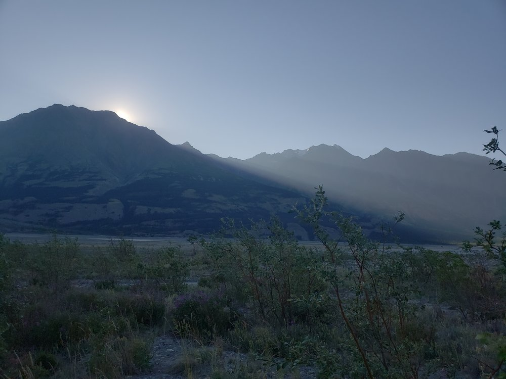 The predawn mountains with rays of sun streaming over the peaks.