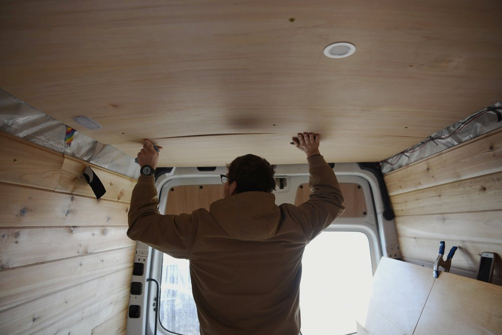 Ian installs a piece of the ceiling paneling. It was helpful to have one person hold the panels while the other person screwed them in.