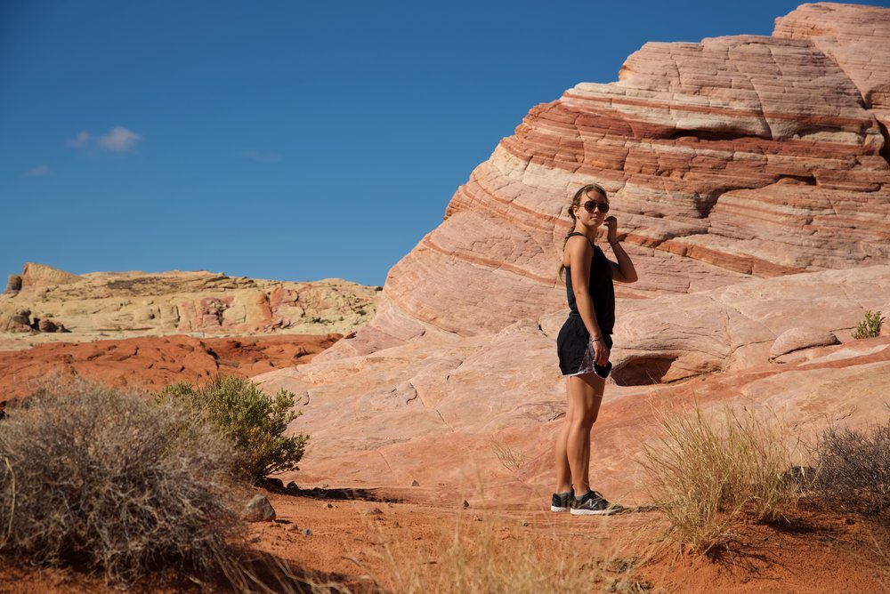 Kaylee exploring the striped sandstone formations of the Fire Wave in Valley of Fire State Park.