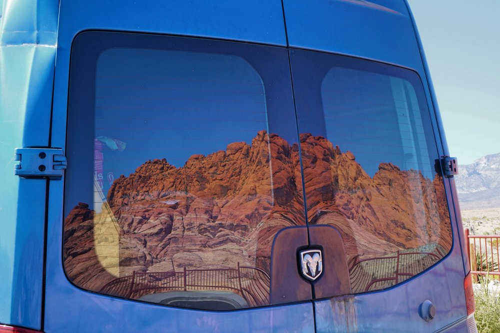 The red Calico Hills reflected in the rear windows of our van.