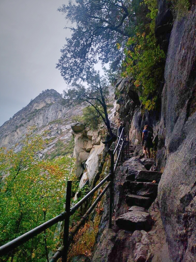 The narrow stone steps built into the rock wall.